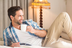 Handsome man relaxing on his bed with hot drink Stock Photos