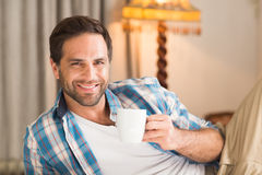 Handsome man relaxing on his bed with hot drink Royalty Free Stock Image