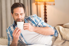 Handsome man relaxing on his bed with hot drink Stock Photography