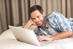 Handsome man relaxing on his bed with laptop Royalty Free Stock Image
