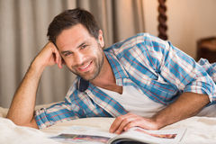 Handsome man relaxing on his bed reading magazine Stock Photography