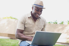Handsome man relaxing in his garden using laptop Royalty Free Stock Photos