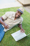 Handsome man relaxing in his garden using laptop to shop Royalty Free Stock Images