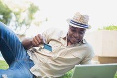 Handsome man relaxing in his garden using laptop to shop Stock Photos