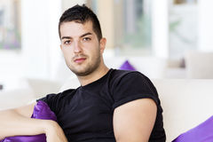 Handsome man relaxing at home on white sofa with purple pillows Stock Photo