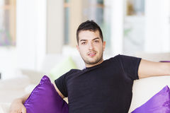 Handsome man relaxing at home on white sofa with purple pillows Royalty Free Stock Image