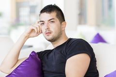 Handsome man relaxing in a hotel lobby on white sofa with purple pillows Stock Photography