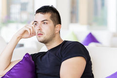 Handsome man relaxing in a hotel lobby on white sofa with purple pillows Royalty Free Stock Photography