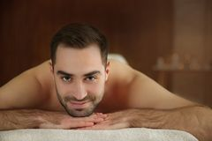 Handsome man relaxing on massage table stock photos