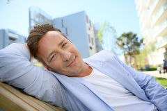 Handsome man relaxing in residential park Royalty Free Stock Photos