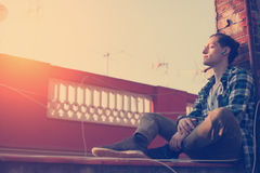Handsome man relaxing on the roof and listening music on his mobile phone. Young and handsome man relaxing on the roof and listening music on his mobile phone Stock Photography