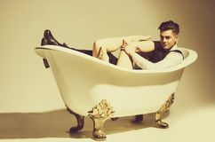 Handsome man relaxing with sexy naked female legs in bath. Handsome happy man or businessman with stylish haircut, hair, in fashion business wear, vest, shirt stock photography