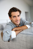 Handsome man relaxing on sofa at home Stock Photography