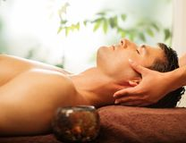 Handsome man relaxing in spa salon Stock Images