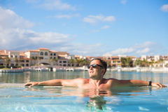 Handsome man relaxing in the swimming pool Stock Photos