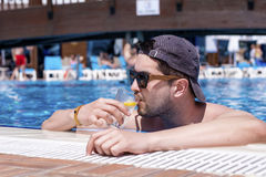 Handsome  man relaxing in the swimming pool with cold  drink. Young smiling  man enjoying his summer vacation  swimming pool Royalty Free Stock Images