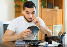 Handsome man remove hair with pincers Royalty Free Stock Photo