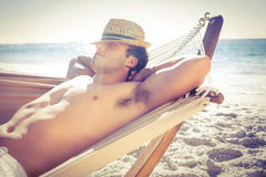 Handsome man resting in the hammock. At the beach Stock Photo