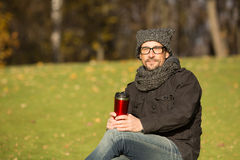 Handsome man resting in the park with a cup of hot tea Royalty Free Stock Image