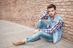 Handsome man resting on the sidewalk, leaning against a wall Stock Images