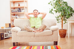 Handsome man resting on sofa at home Stock Images