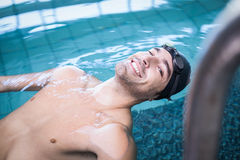 Handsome man resting in the water. In the pool Stock Images