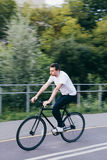 Handsome man rides fixie bike Stock Images