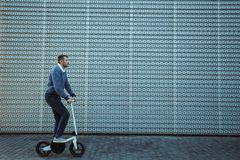 Man riding scooter in front of the modern facade stock images