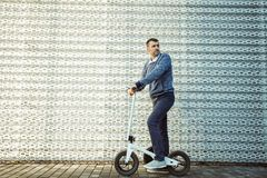 Man standing with scooter against the background of the steel facade stock image