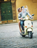 Handsome man riding a scooter with his girlfriend. Handsome guy riding a scooter with his girlfriend Stock Photography