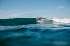 Handsome man riding waves on surfboard while. Having vacation royalty free stock image