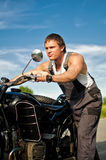 Handsome man rolling a motorcycle. Royalty Free Stock Photography