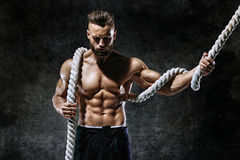 Handsome man with rope. Photo of young man with muscular topless body. Strength and motivation Stock Photography