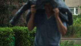 Handsome man is running across the street and hiding from the rain under his jacket. No focus, HD stock video footage