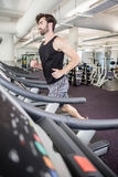 Handsome man running on treadmill Stock Photography