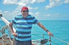 Handsome man sailing. A handsome, healthy, white middle aged male enjoys a sunny afternoon tall ship sailing in the Exumas Stock Image