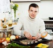 Handsome man salting fish on baking sheet Royalty Free Stock Photography