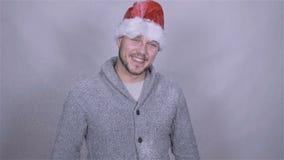 Handsome man in santa claus hat enjoying snow, slow motion. stock footage