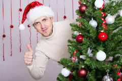 Handsome man in santa hat thumbs up and decorated Christmas tree Stock Photography