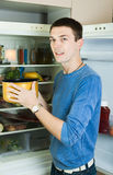 Handsome man with saucepan near refrigerator stock photos