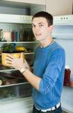 Handsome man with saucepan  near refrigerator Stock Photos