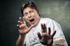 Handsome man scared over dark grey. Background Stock Photography