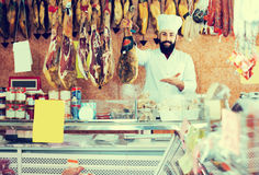 Handsome man seller showing jamon Royalty Free Stock Photo