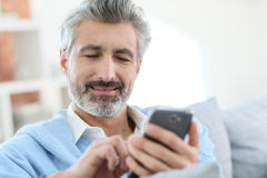 Handsome man sending message with smartphone Stock Photography