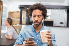 Handsome man sending a text drinking coffee Royalty Free Stock Photos