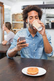 Handsome man sending a text drinking coffee Royalty Free Stock Photo