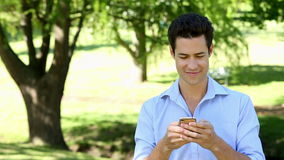 Handsome man sending a text in the park stock video footage