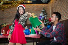 Handsome man sent green gift bag to beautiful woman, who wear red dress and santa claus hat at the party. stock photo