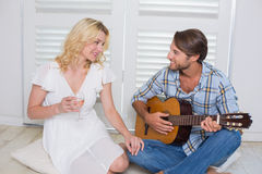 Handsome man serenading his girlfriend with guitar Stock Image