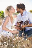 Handsome man serenading his girlfriend with guitar Royalty Free Stock Images